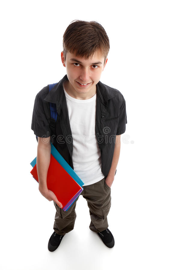 Student holding books. A male teenage student standing in casual clothes and holding some books in one hand. White background royalty free stock photography