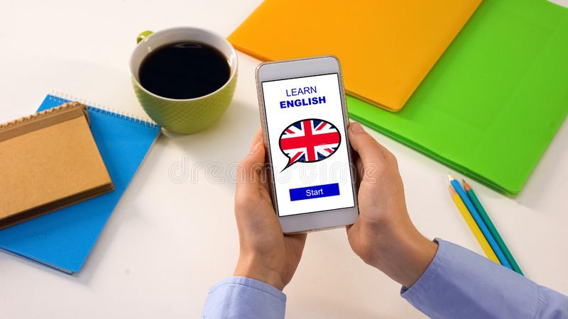 Student holding cellphone with learn English app, online education, language. Stock photo royalty free stock photo