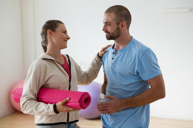 Student holding exercise mat talking to instructor in health club royalty free stock photography