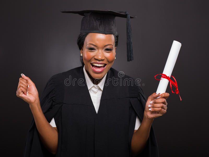 Student holding graduation certificate. Excited african university student holding her graduation certificate royalty free stock photography