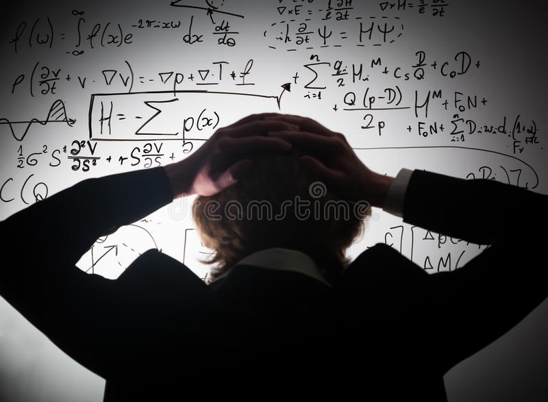 Student holding his head looking at complex math formulas on whiteboard. Problem to solve stock photo