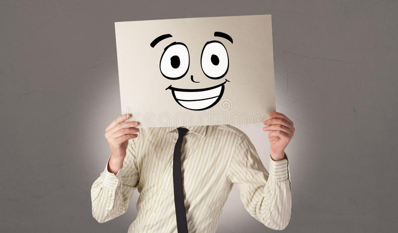 Student holding a paper with laughing emoticon in front of his face. Young student holding a paper with laughing emoticon in front of his facen stock photos
