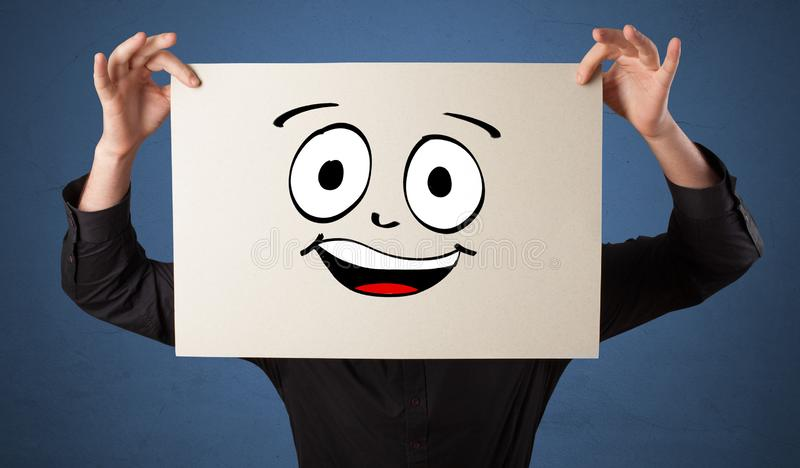 Student holding a paper with laughing emoticon in front of his face. Young student holding a paper with laughing emoticon in front of his facen royalty free stock photography