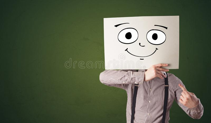 Student holding a paper with laughing emoticon in front of his face. Young student holding a paper with laughing emoticon in front of his facen royalty free stock photo