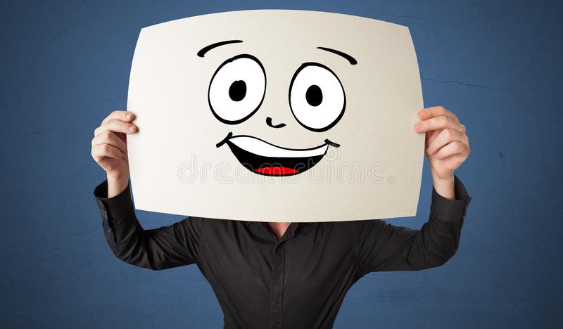 Student holding a paper with laughing emoticon in front of his face. Young student holding a paper with laughing emoticon in front of his facen stock image