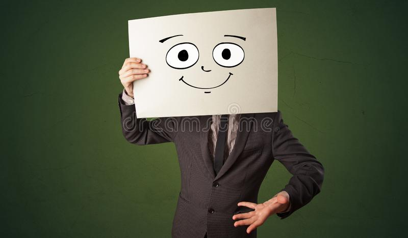 Student holding a paper with laughing emoticon in front of his face. Young student holding a paper with laughing emoticon in front of his facen stock images