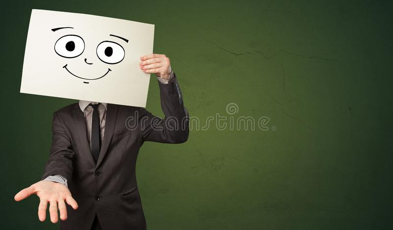 Student holding a paper with laughing emoticon in front of his face. Young student holding a paper with laughing emoticon in front of his face royalty free stock image