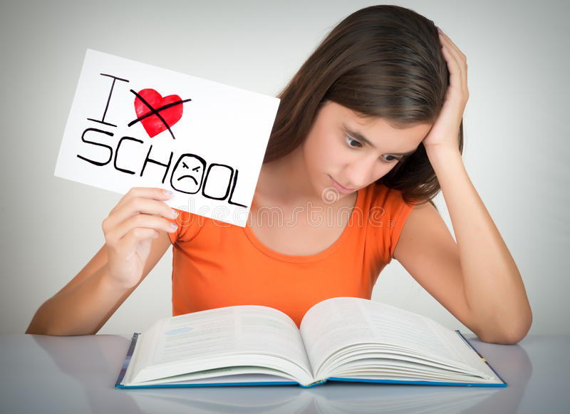 Student holding a sign with the words I hate school. Girl studying and holding a sign with the words I hate school stock photography
