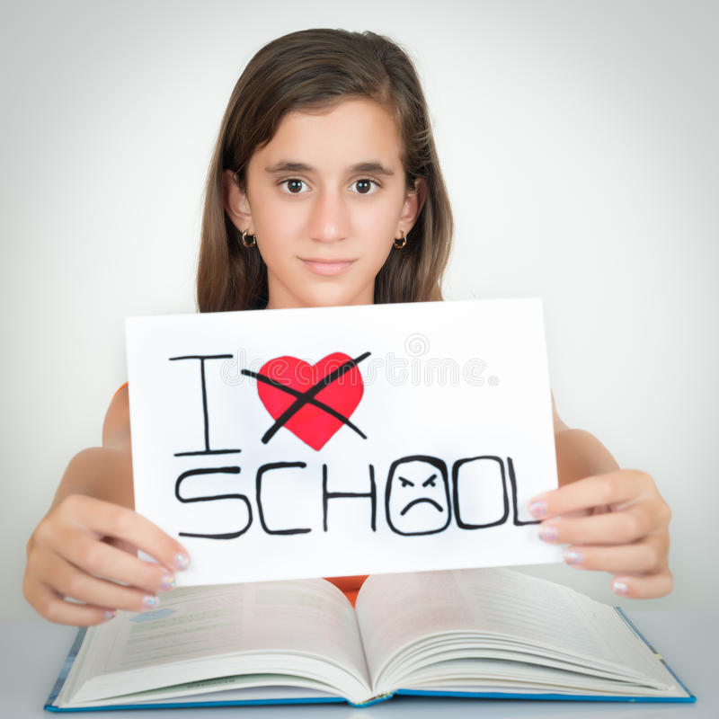 Student holding a sign with the words I hate school. Girl studying and holding a sign with the words I hate school stock images