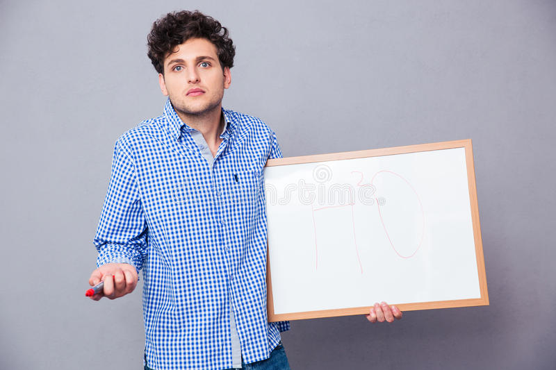 Student holding text board. Young male student holding text board with marker and shrugging royalty free stock image