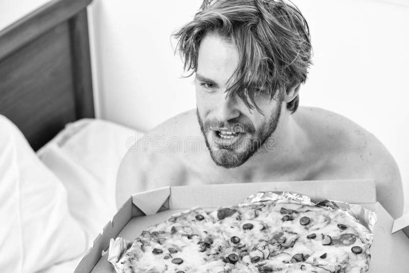 Student is at home on the bed in a bright apartment eating a tasty pizza. Break diet concept. Man likes pizza for. Breakfast. Bed pizza stock photography