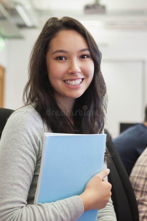 Student i en datasal som rymmer en mapp royaltyfria foton