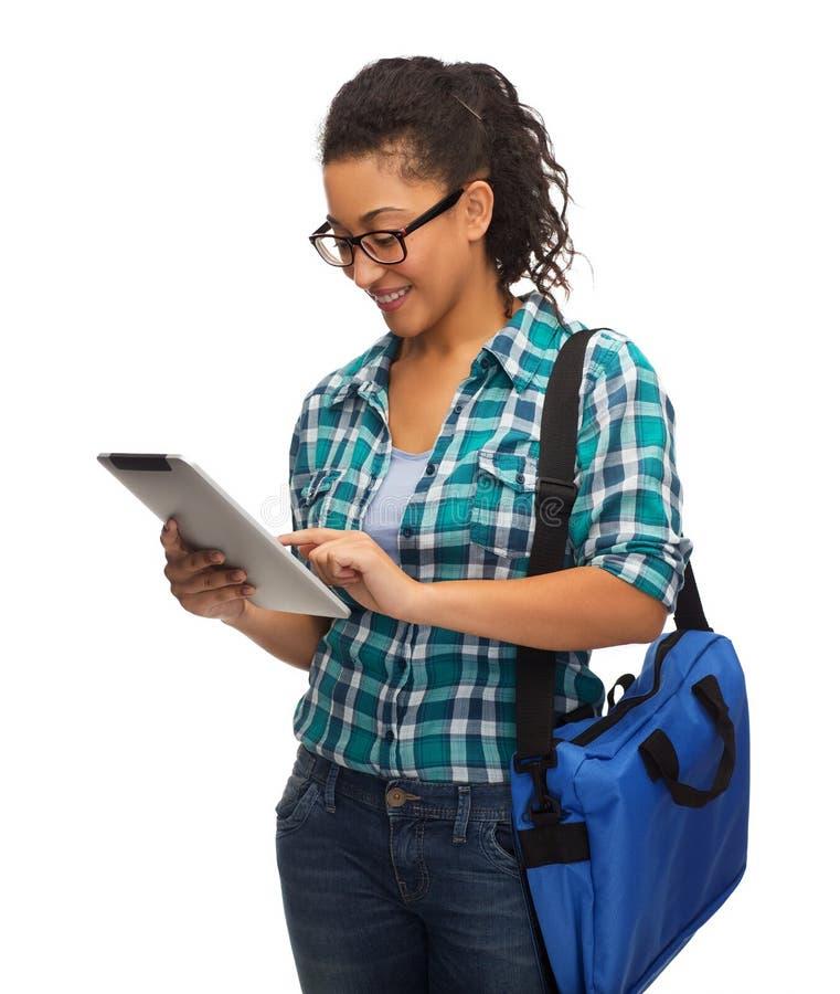 Student i glasögon med den minnestavlaPC och påsen royaltyfri foto
