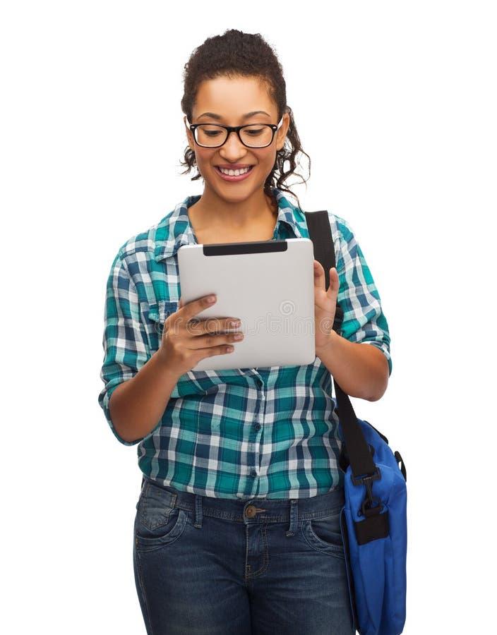 Student i glasögon med den minnestavlaPC och påsen royaltyfria bilder