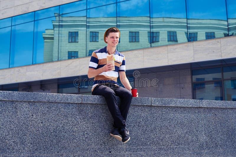 Student i hörlurar som har lunch, medan sitta på stenväggen arkivfoton