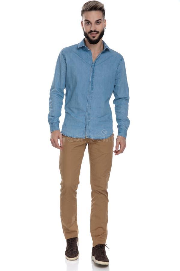 Student i jeansskjortaanseende med händer nära kropp royaltyfria foton