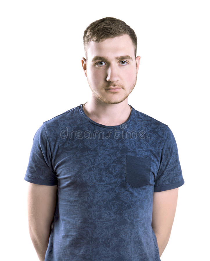 A student isolated on a white background. A young man posing in a dark blue t-shirt. A strong guy with a neutral expression. stock photography