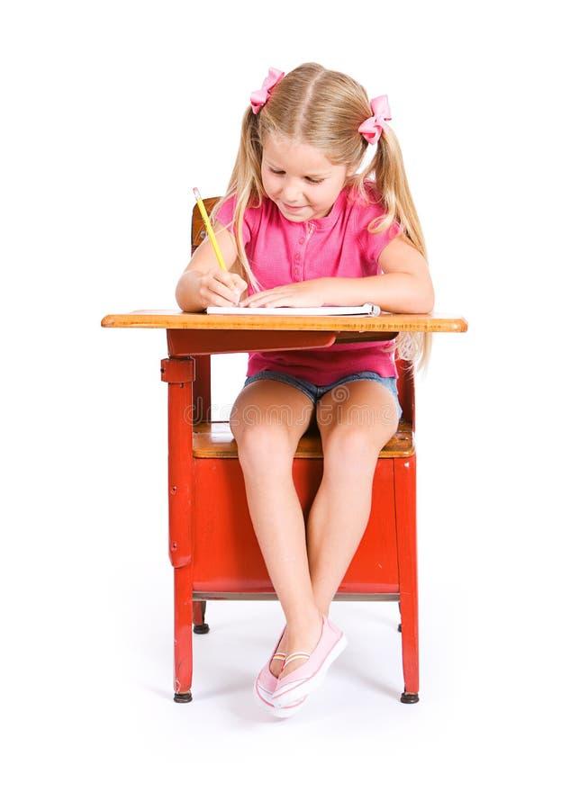 Student: Junge Studentin Works On Assignment im Notizbuch lizenzfreie stockfotos