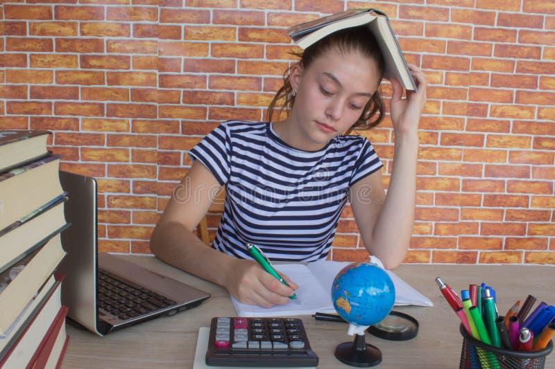 Student, junges Mädchen, das an seiner Hausarbeit arbeitet Porträt des hohen studierenden und schreibenden Schülers des hübschen  stockbild