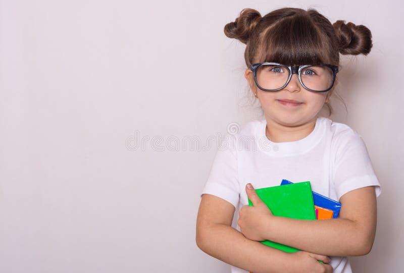 Student klaar voor school De Kantoorbehoeften van kinderen voor school Jong geitje met notitieboekje en pen in handen stock afbeelding