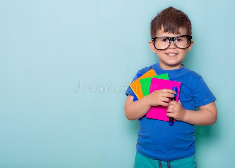 Student klaar voor school De Kantoorbehoeften van kinderen voor school Jong geitje met notitieboekje en pen in handen stock afbeeldingen