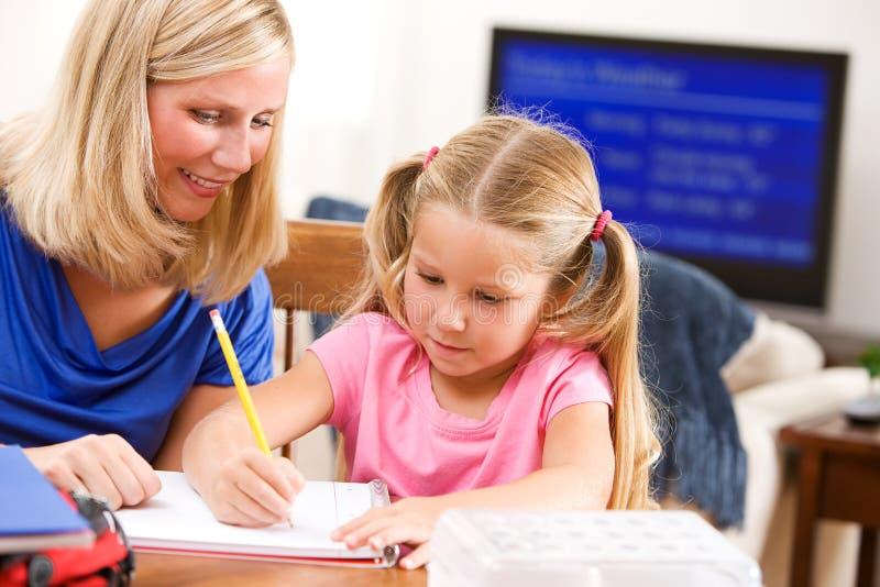 Student: Kleines Mädchen-Fertigungshausarbeit durch  stockfoto