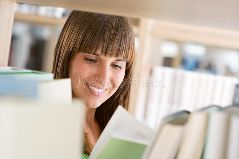 Student in library - cheerful woman read book. Stand by bookshelf stock image
