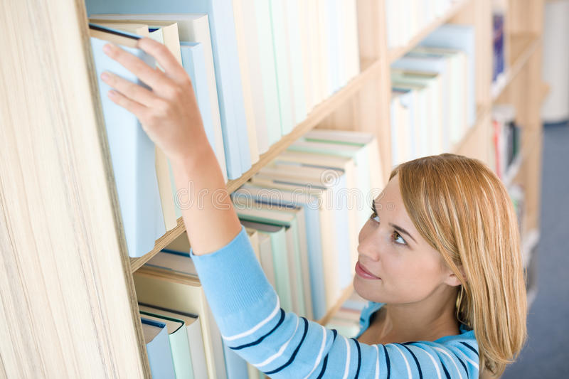 Student in library - happy woman reach for book. From bookshelf royalty free stock photography