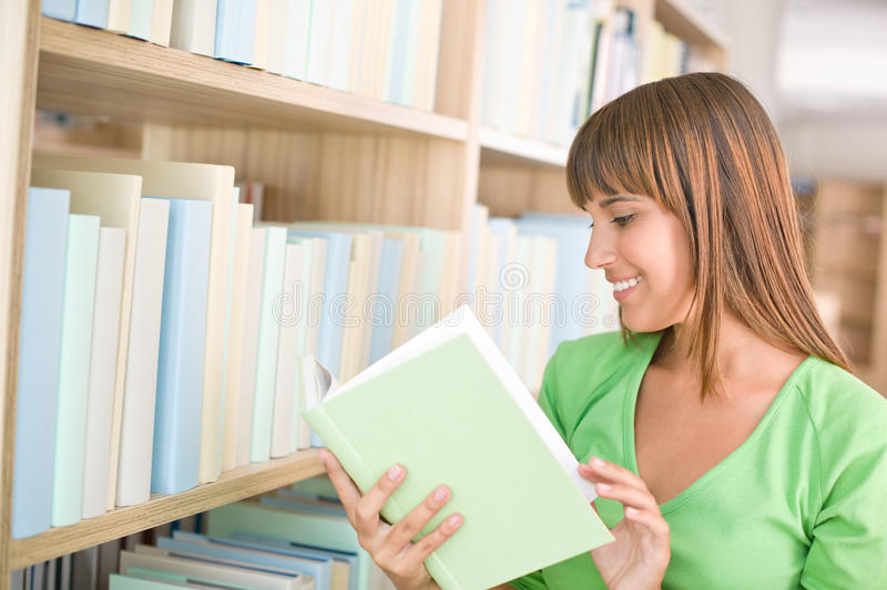Student in library - happy woman read book. From bookshelf royalty free stock image