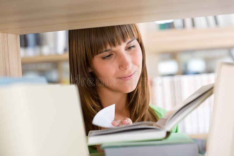 Student in library - happy woman read book. Stand at bookshelf stock image