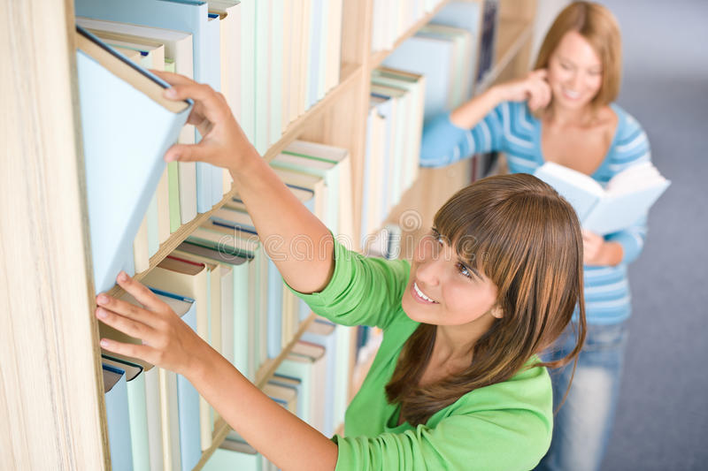 Student in library - two happy woman choose book. From bookshelf stock photo