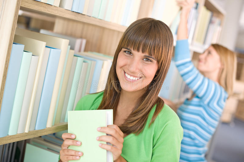 Student in library - two woman choose book. From bookshelf royalty free stock photos