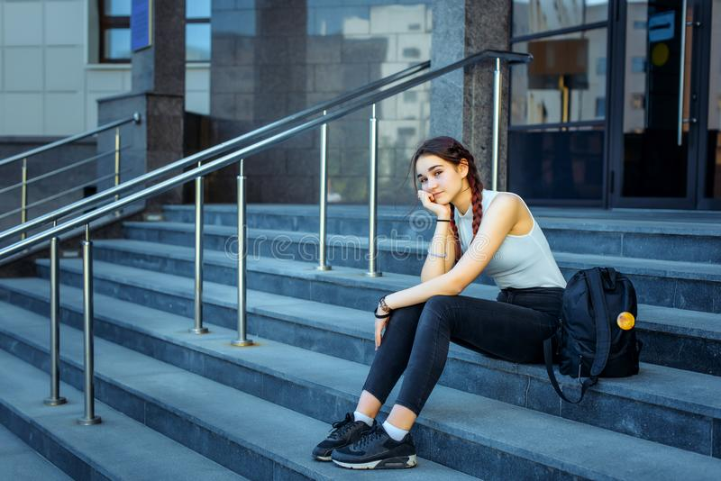 Student life, exams, sessions. Schoolgirl with a backpack sitting on the steps of the institution.  royalty free stock photo