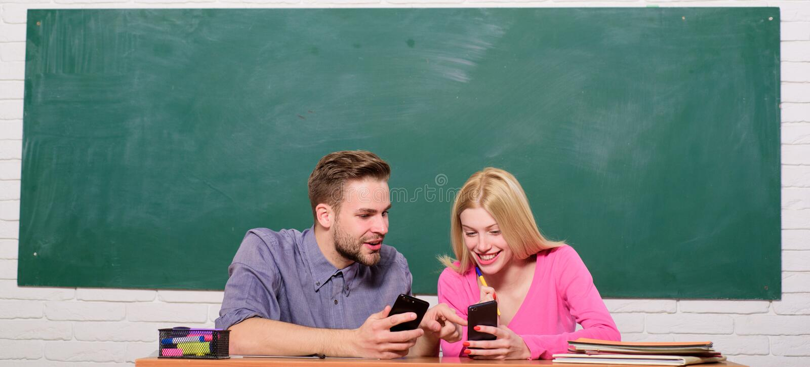 Student life. Lesson and blackboard. Teachers day. Modern school. Knowledge day. Couple of man and woman in classroom royalty free stock image