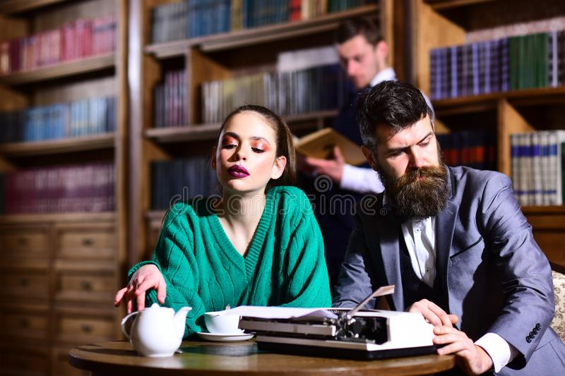 Student life in university. couple in library with typewriter and teapot drinking coffee from cup. literature cafe with. Bearded men and cute girl.agile stock photo