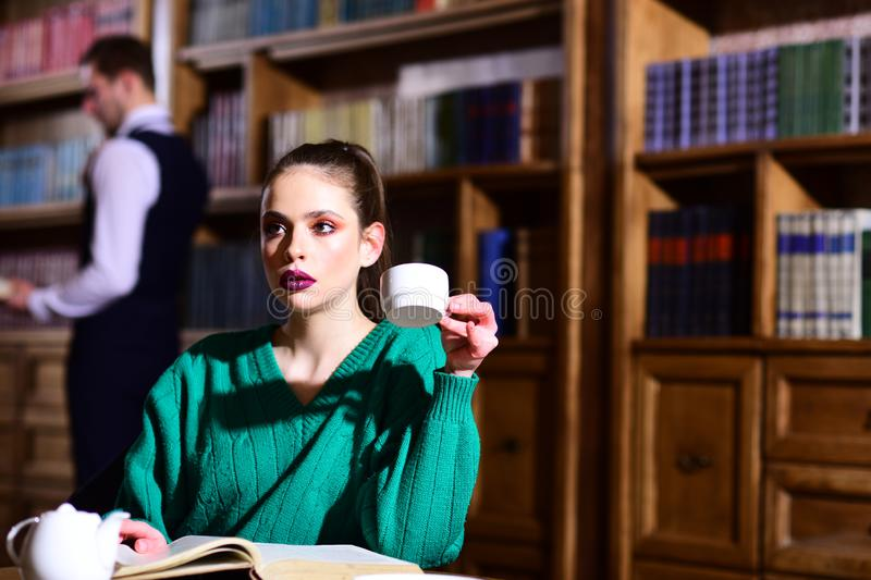 Student life in university. woman in library read book at teapot drinking coffee from cup. literature cafe with cute royalty free stock image
