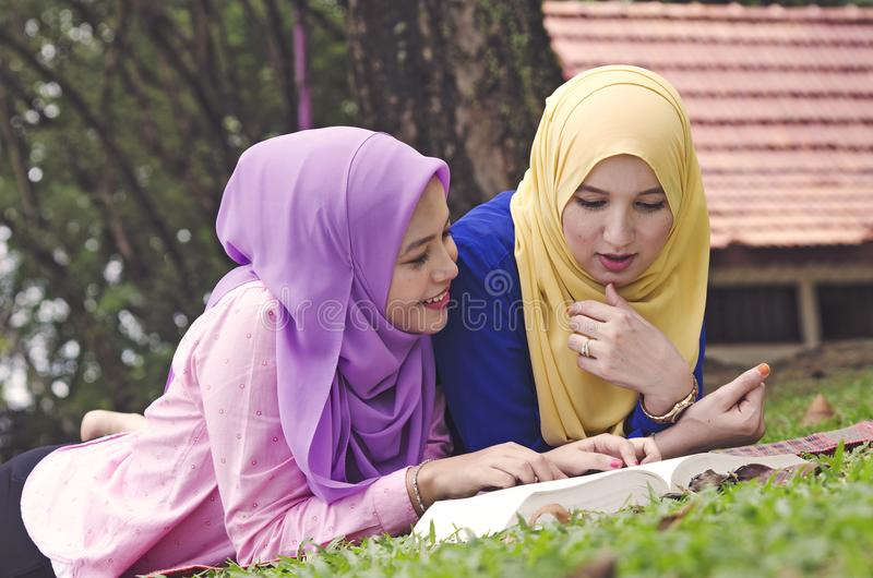 Student lifestyle, happy hijab women laying and read book stock photo