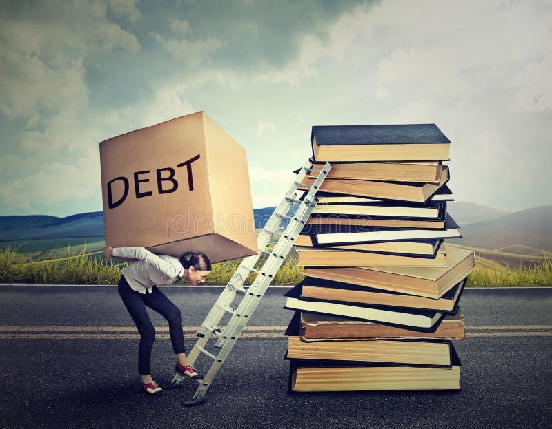 Student Loan Debt Frau mit der schweren Kastenschuld, die es herauf Bildungsleiter trägt lizenzfreie stockfotografie