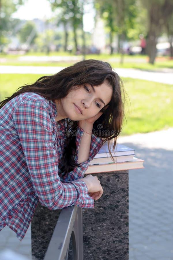 Student macht sich über Lehrbücher im Park Sorgen lizenzfreies stockbild