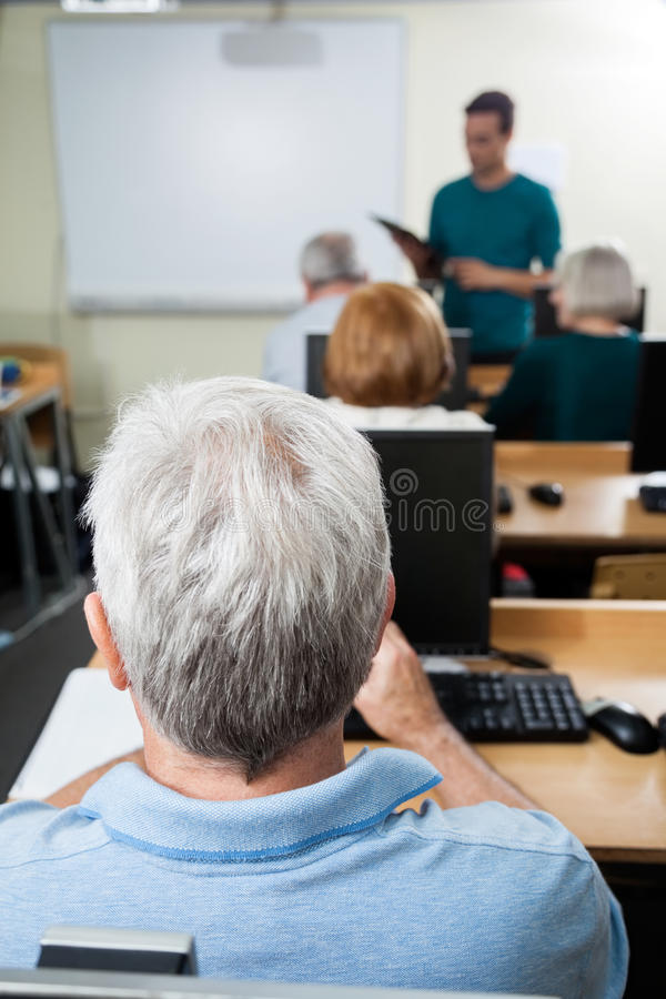 Student With Male Teacher In Computer Class royalty free stock photos