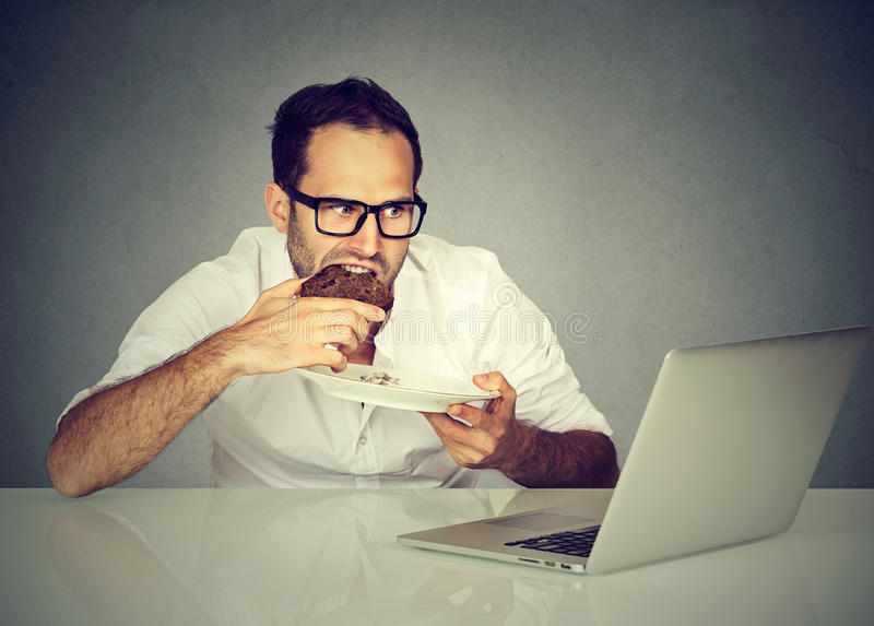 Student man eating while working on laptop. Young student man eating while working on laptop royalty free stock photos