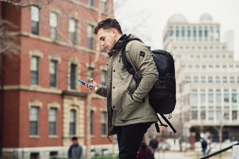 Student man text on cell phone walking in city college campus with backpack. Student man text on cell phone walking in city college campus with backpack royalty free stock image