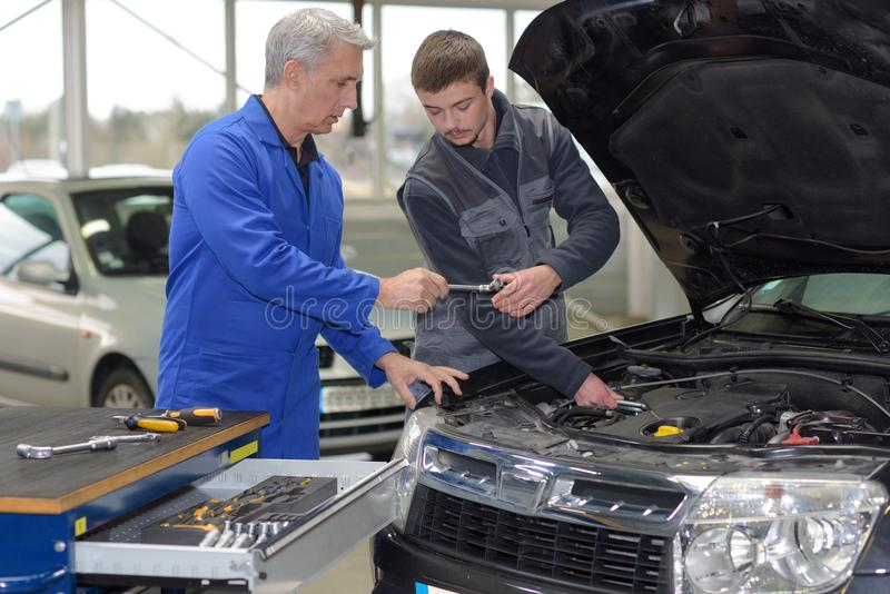 Student mechanic learning from teacher in automotive vocational school. Trainee royalty free stock photos