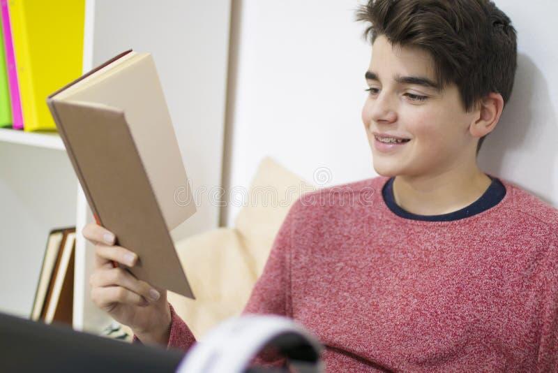 Student med boken hemma arkivfoton