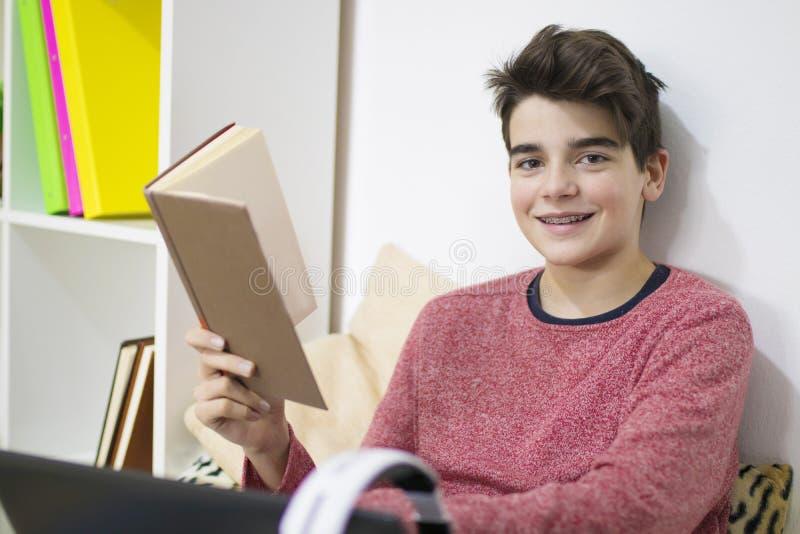 Student med boken hemma royaltyfri foto