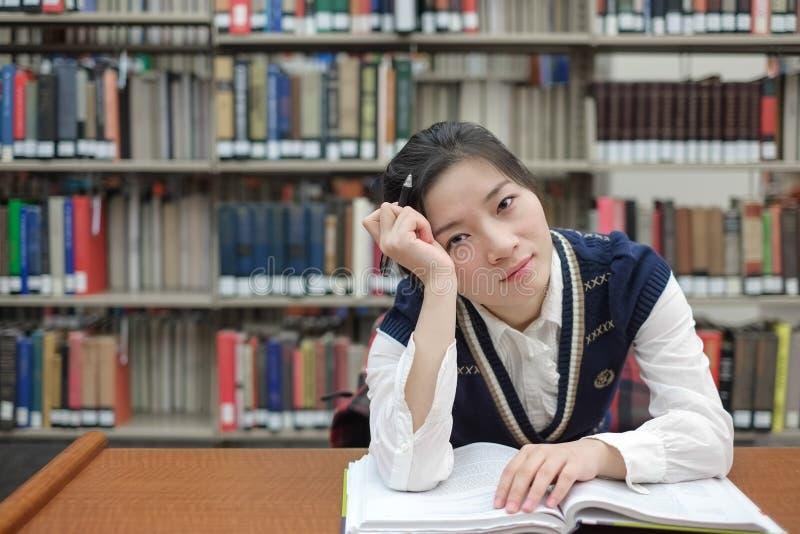 Student med den öppna läroboken som är djup i tanke royaltyfri foto