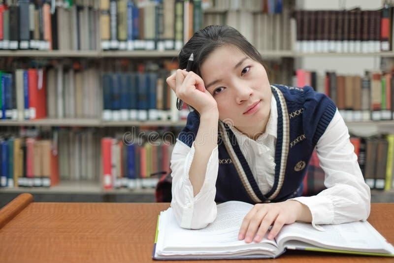 Student med den öppna läroboken som är djup i tanke royaltyfri bild