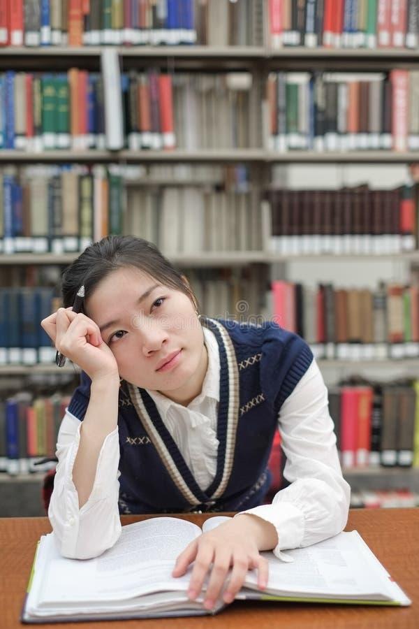 Student med den öppna läroboken som är djup i tanke arkivbilder