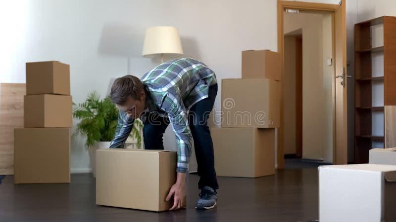 Student med den ledsna framsidan som lämnar sovsalen som tar asken med hans material, avläggande av examen royaltyfri bild