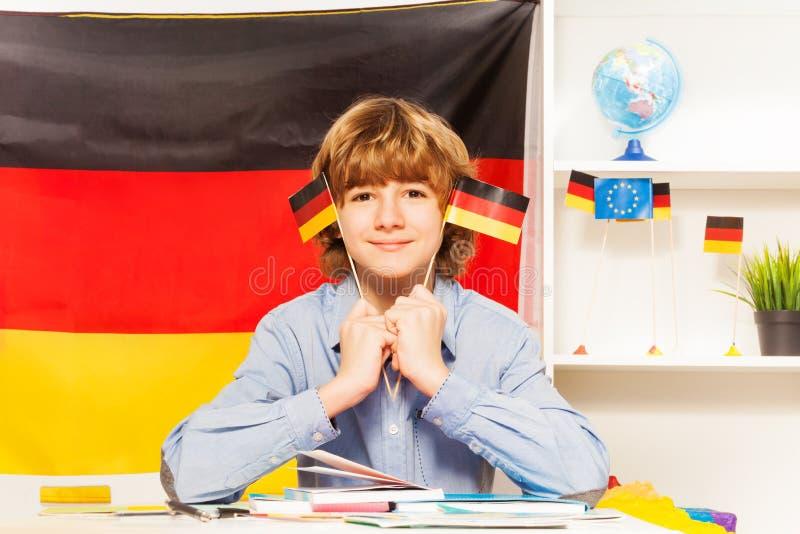 Student med två flaggor av Tysklandsammanträde på grupp royaltyfri fotografi